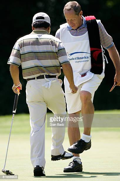 Massy Kuramoto of Japan and his caddie Terry Travis give each other 'low fives' after Kuramoto's birdie putt on the first green during the second...