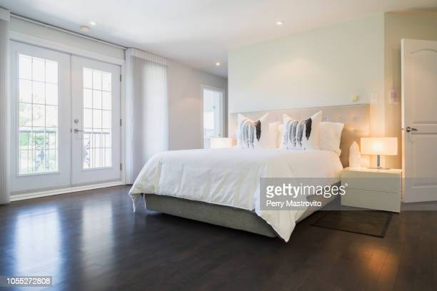 master bedroom with queen size bed and dark wooden flooring, upstairs inside luxury residential home - 寝室 ストックフォトと画像
