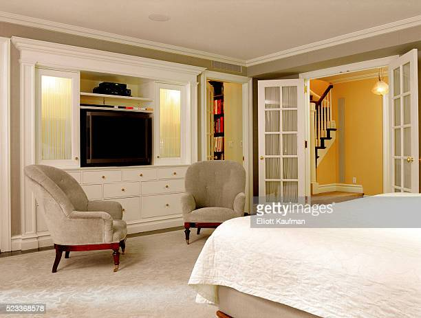 Master bedroom with television hidden in wall unit