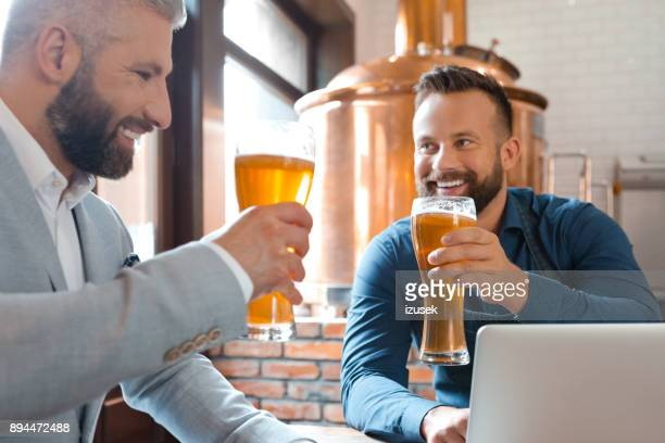 master brewer and businessman having beers in brewery - microbrewery stock photos and pictures