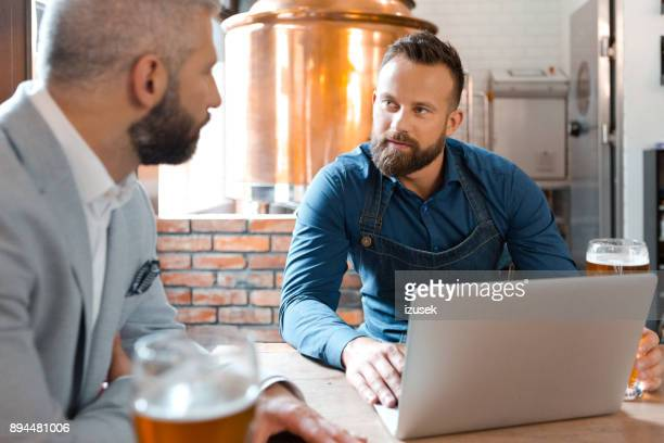 master brewer meeting with businessman in brewery - izusek stock pictures, royalty-free photos & images