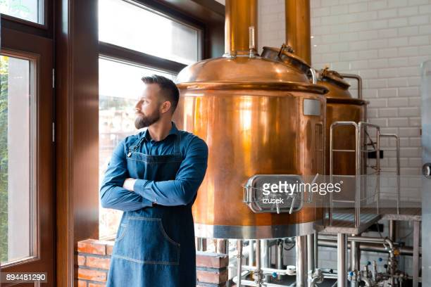 master brewer standing in micro brewery - brewery stock pictures, royalty-free photos & images