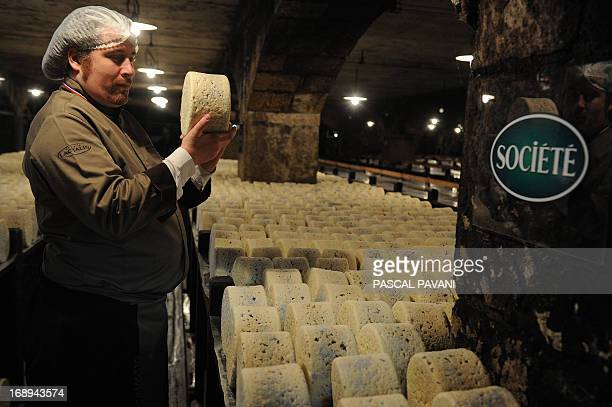 A master cheese maker controls the quality of cheeses at the Roquefort Societe company on May 16 2013 in a cellar at RoquefortsurSoulzon southern...
