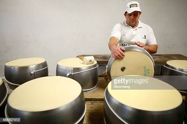 A master cheesemaker turns a whole cheese encased in a 'fascera' mould during the ParmigianoReggiano cheese manufacturing process at Coduro...