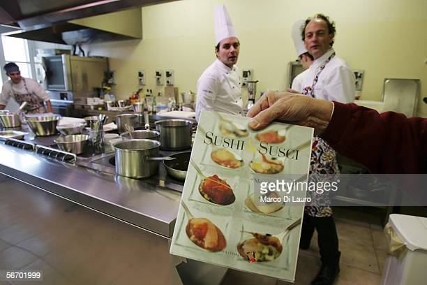 Master Chef Moreno Cedroni of the La Madonnina del Pescatore of Senigallia restaurant is seen in the background of his latest book Sushi and Susci...