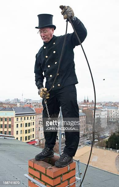 Master chimneysweep Norbert Skrobek demonstrates his trade using a coiledwire brush on a rooftop in Berlin's Kreuzberg district December 27 2012 A...