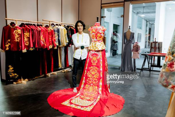 master chinese wedding dress designer in studio with garment - fashion industry stock pictures, royalty-free photos & images