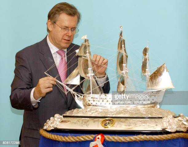 Master craftsman Richard Jarvis inspects detail of a sterling silver model of Lord Nelson's Trafalgar flagship HMS Victory on display in London...