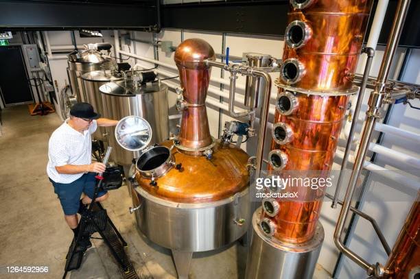 master distiller working at a craft distillery - vodka stock pictures, royalty-free photos & images