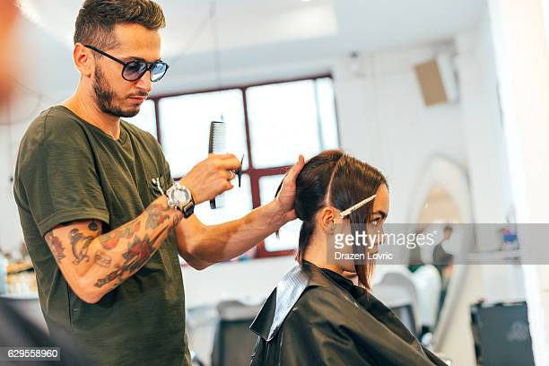 Master hair stylist cutting woman's hair with electronic trimmer