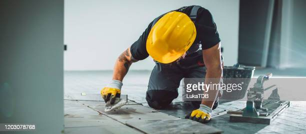 master installer laying tile - building contractor stock pictures, royalty-free photos & images