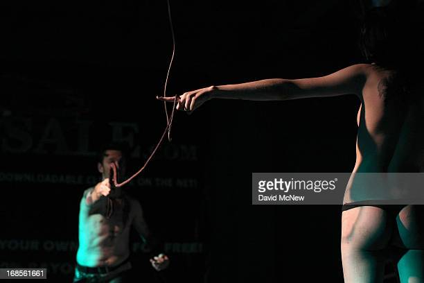 Master Nik wraps a whip around the finger of a voluntarily submissive woman at a dungeon party during the domination convention DomCon LA in the...