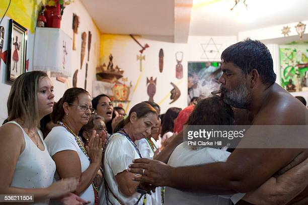 Master of ceremonies Babalawo hugs one of the adherants at a Ceremony at Terreiro peace and love / Terreiro Paz y Amor Salvador Bahia Brazil Often...