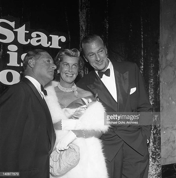 Master of ceremonies George Jessel greets actor Gary Cooper and his wife Veronica Cooper at the premiere of the Warner Bros film 'A Star Is Born' on...