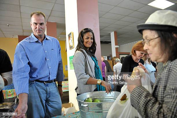 Master of Ceremonies Jay Bilas and Boxer Laila Ali pass out food to residents of the Tenderloin district at the Feeding America Food Bank on October...