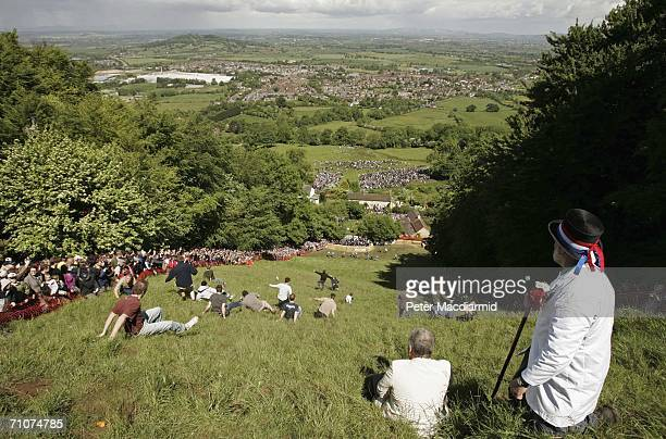 Master of Ceremonies Rob Seex watches a Cheese Rolling race on Coopers Hill on May 29 2006 in Gloucesters England The annual tradition which is...