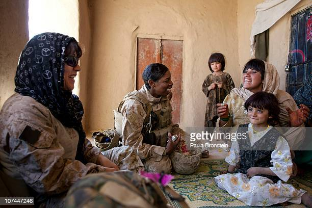 Master Sargent Cherelle PetersWilliams US Marine with the FET 1st Battalion 8th Marines Regimental Combat team II speaks with an Afghan woman and her...