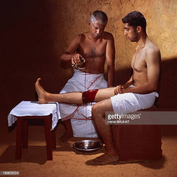 Master Sherif is pouring on his patient's knee some sesam oil laced with ghee in order to cure him from a kneecap inflammation This ayurvedic...