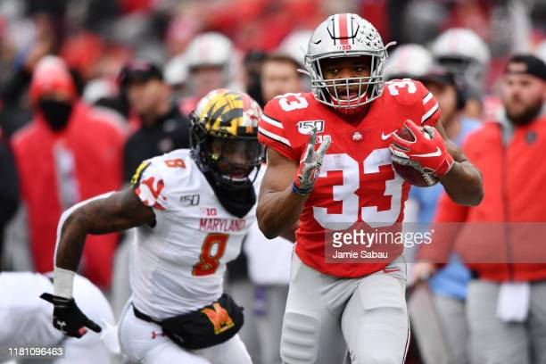 Master Teague III of the Ohio State Buckeyes takes off on a 30yard run in the second quarter as Marcus Lewis of the Maryland Terrapins gives chase at...