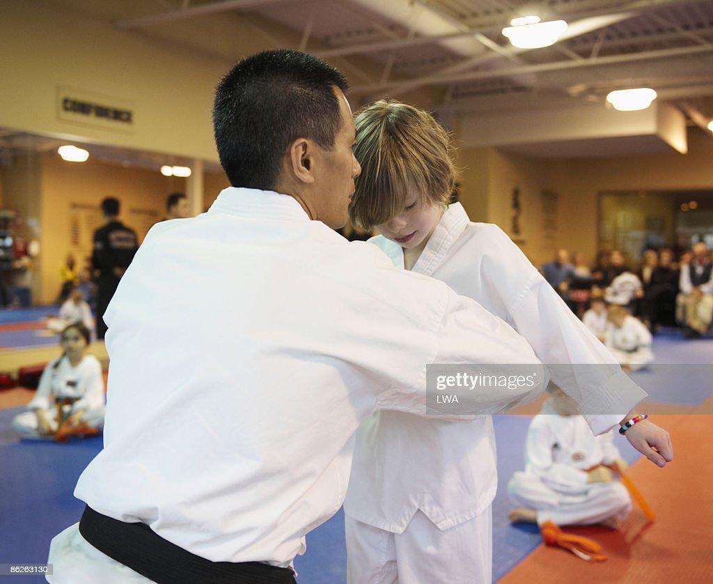 Master Tying Belt On Tae Kwon Do Student : Stock Photo