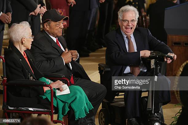 Master violinist and teacher Itzhak Perlman maneuvers his electric scooter into place next to pioneering NASA mathematician Katherine Johnson and...