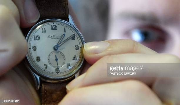 Master watchmaker Matthias Beck moves the hands of a vintage wrist watch on March 19 2018 at the German Clock Museum in Furtwangen southern Germany...