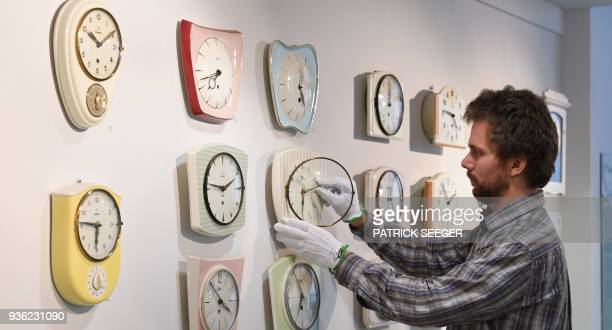 Master watchmaker Matthias Beck moves the hands of some vintage kitchen clocks on March 19 2018 at the German Clock Museum in Furtwangen southern...