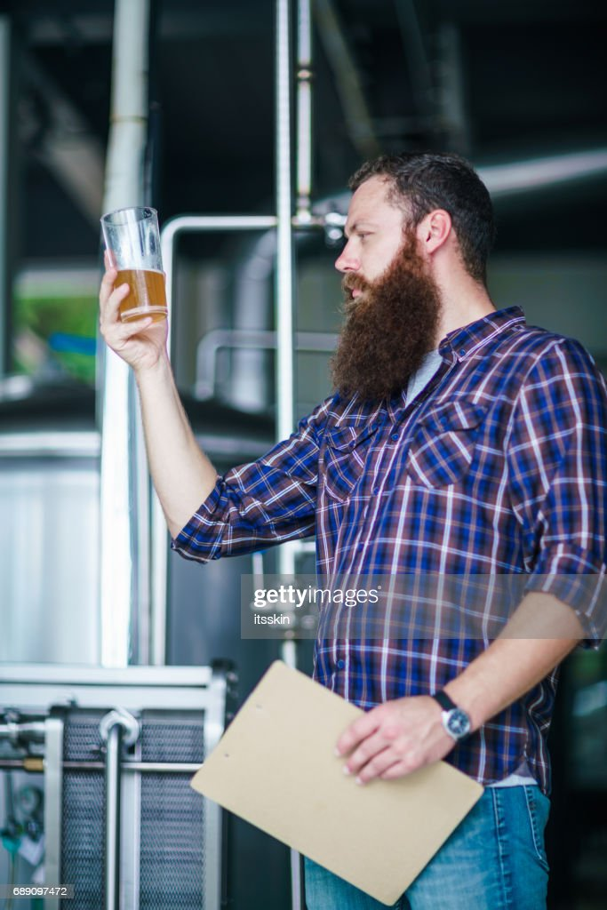Master works in the brewery: beer testing, making remarks, quality control : Stock Photo