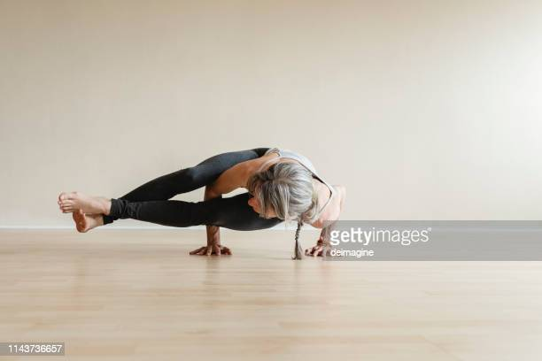 master yoga woman doing eight-angle pose, astavakrasana. - active lifestyle stock pictures, royalty-free photos & images
