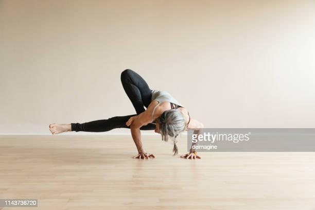 master yoga woman doing grasshopper pose, parsva bhuja dandasana. - solid stock pictures, royalty-free photos & images