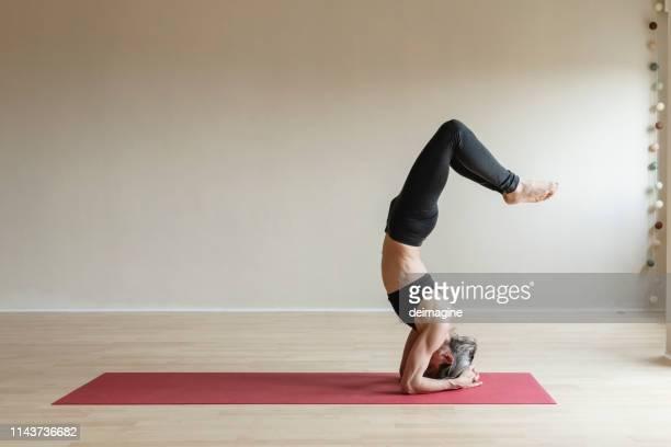 master yoga woman doing headstand, sirsasana. - yogi stock pictures, royalty-free photos & images