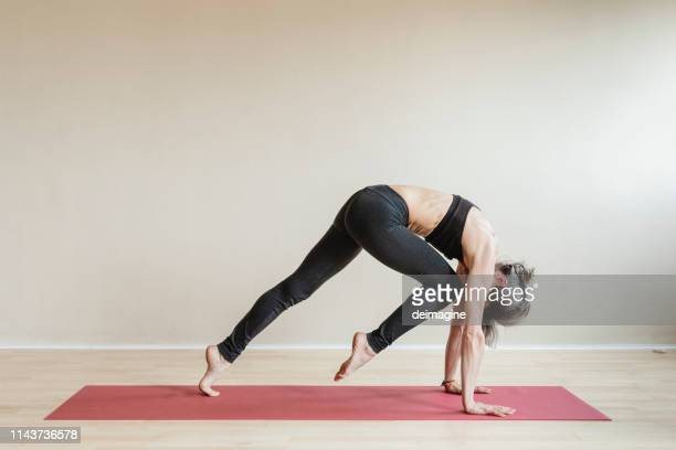 master yoga woman doing plank pose variation knee to nose, phalakasana variation knee to nose. - yoga studio stock pictures, royalty-free photos & images