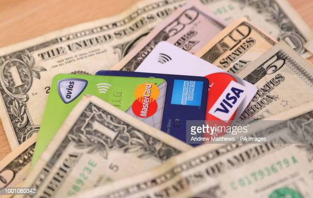A Mastercard American Express and Visa credit and debit cards surrounded by US Dollars
