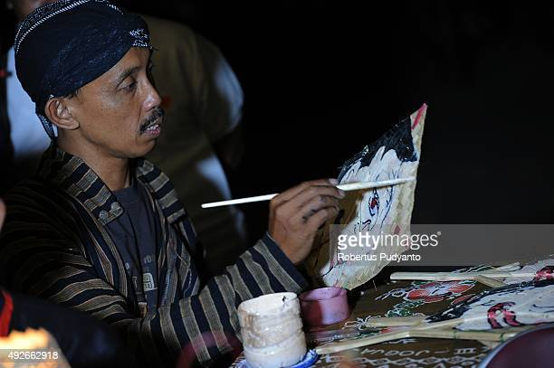 A mastermind paints a wayang tepas during the 1437th AlHijra Islamic New Year celebration at Keraton Surakarta Hadiningrat on October 14 2015 in Solo...