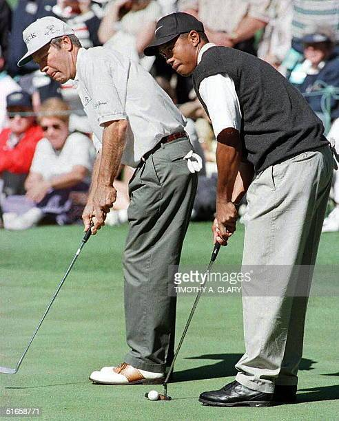 Masters champion Ben Crenshaw and Tiger Woods putt on the 16th hole 09 April during the final practice round for the Masters golf tournament at the...