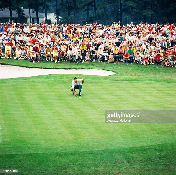 Masters Champion Bob Goalby lines up his putt on the 18th green in front of a large gallery during the 1968 Masters Tournament at Augusta National...