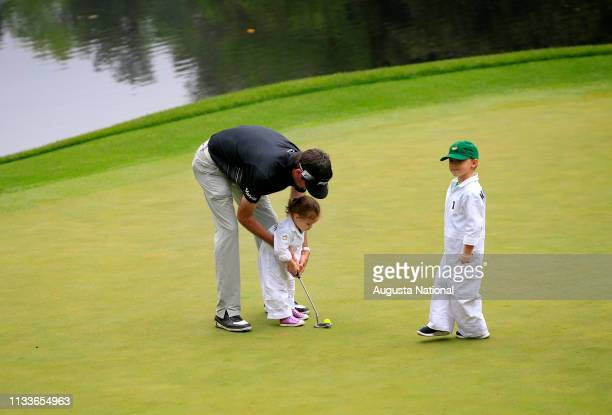 Masters champion Bubba Watson helps his daughter Dakota and son Caleb on the ninth hole during the Par 3 Contest at Augusta National Golf Club...