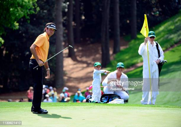 Masters champion Bubba Watson putts on the No. 1 as his wife Angie and son Caleb look on during the Par 3 Contest for the Masters at Augusta National...