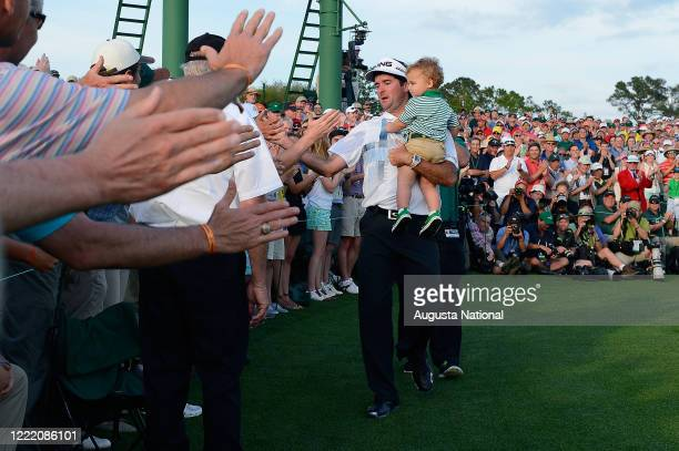 Masters champion Bubba Watson reacts with patrons as he holds son Caleb after winning the Masters during the final round at Augusta National Golf...
