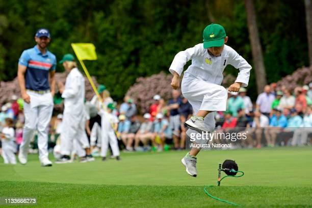 Masters champion Bubba Watson son Caleb jumps over a boom microphone and cable during the Par 3 Contest at Augusta National Golf Club, Wednesday,...