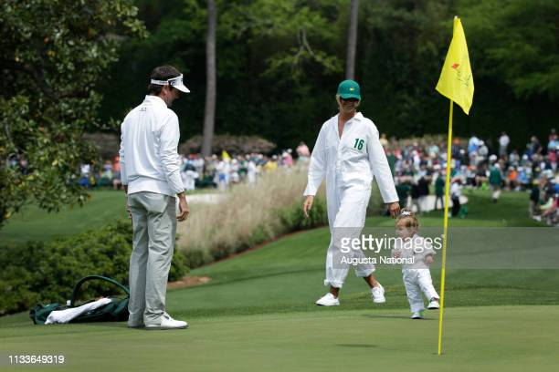 Masters champion Bubba Watson watches his daughter Dakota walk with his wife Angie during the Par 3 Contest at Augusta National Golf Club on...