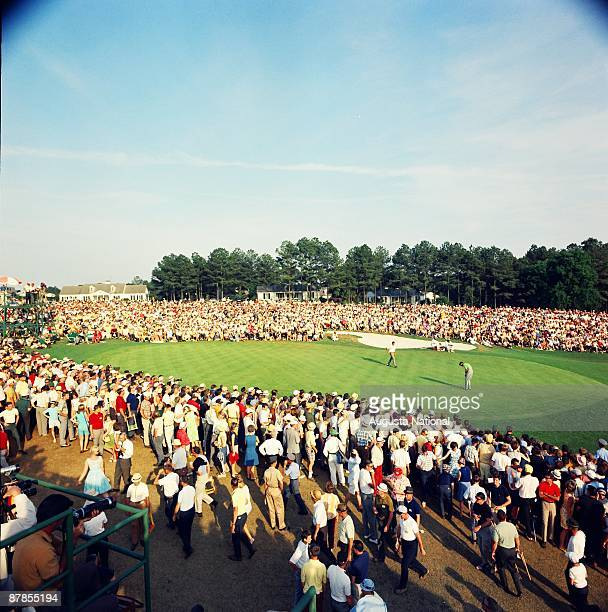 Masters Champion Gay Brewer and Runnerup Bobby Nichols play the 18th green in front of a large gallery during the 1967 Masters Tournament at Augusta...