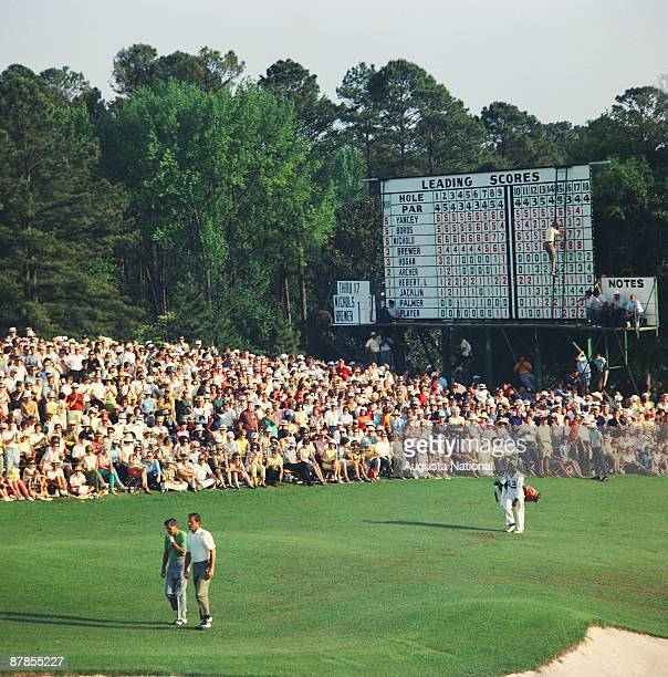 Masters Champion Gay Brewer and Runnerup Bobby Nichols walk up the 18th fairway in front of a large gallery during the 1967 Masters Tournament at...