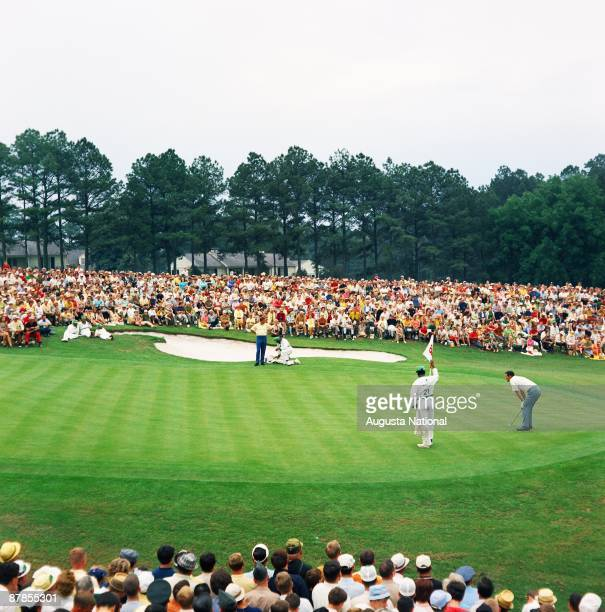 Masters champion Gay Brewer lines up his putt on the 18th green in front of a large gallery during the 1967 Masters Tournament at Augusta National...