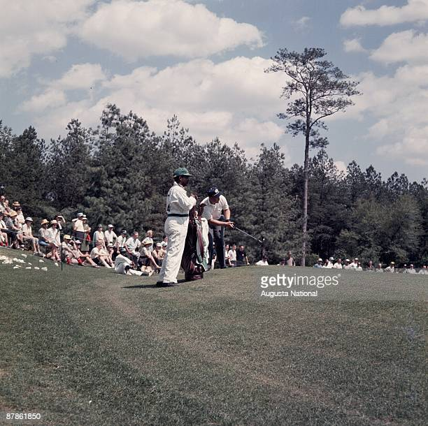 Masters Champion Jack Nicklaus hits from the edge of the green with his caddie during the 1963 Masters Tournament at Augusta National Golf Club on...