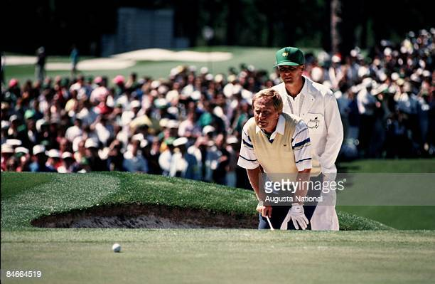 Masters Champion Jack Nicklaus lines up his putt with the help of his caddie during the 1990 Masters Tournament at Augusta National Golf Club on...