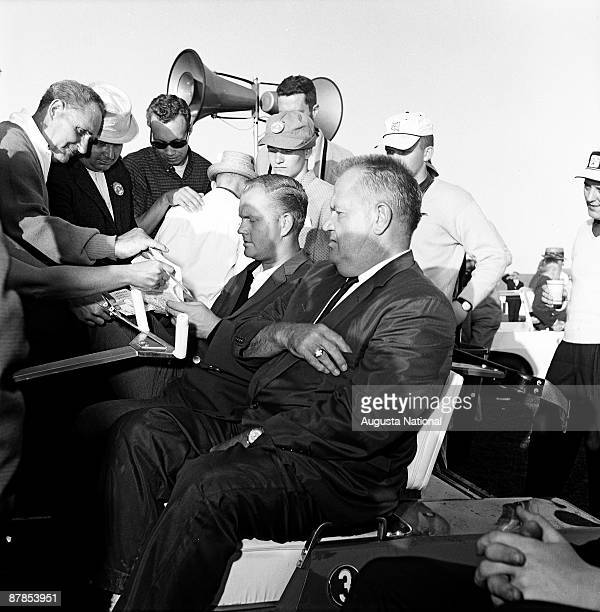 Masters Champion Jack Nicklaus signs autographs while seated next to his father Charlie during the 1963 Masters Tournament at Augusta National Golf...