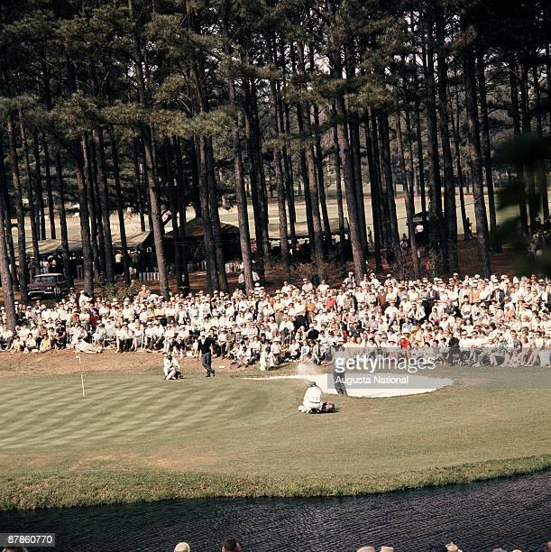 Masters Champion Jack Nicklaus watches George Bayer blasts out of the bunker during the 1963 Masters Tournament at Augusta National Golf Club on...