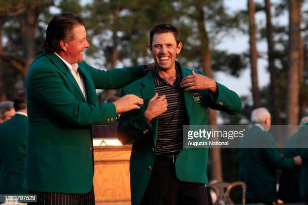 Masters champion Phil Mickelson of the United States helps 2011 Masters Tournament winner Charl Schwartzel of South Africa at the Green Jacket...
