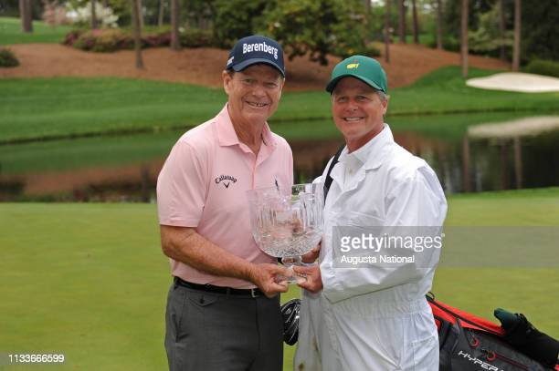 Masters champion Tom Watson and his caddie hold the Crystal Pedestal Bowl aloft after winning the Par 3 Contest at Augusta National Golf Club...
